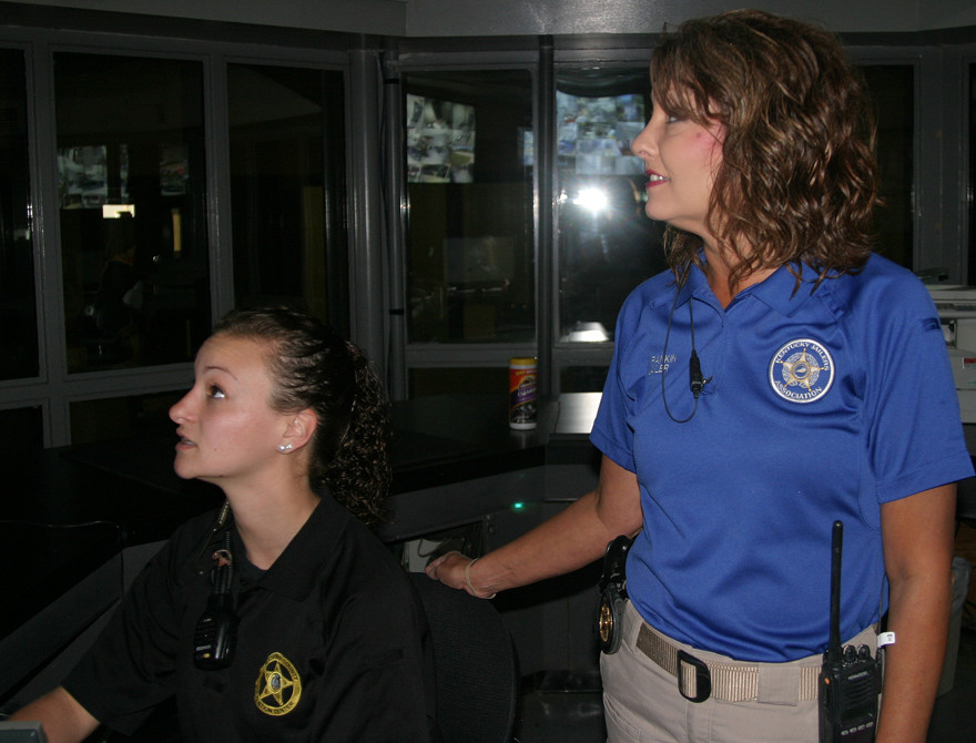 WOODFORD JAILER Michele Rankin, right, with jail employee Madison Venturini, takes a look at one of the many monitors showing images from cameras stationed around the Woodford County Detention Center. Rankin is one of two female members of the Kentucky Jailers Association's Board of Directors. (Photo by John McGary)