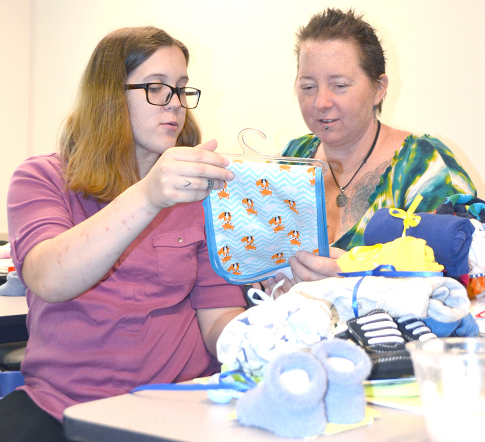 MEGAN PRATHER and her mom, Christina Prather, looked at the clothes and many other baby items in her Little Man's Legacy Tote during a special birthday party at the Woodford County Health Department Monday morning. Giving totes to expectant moms help Pat Roberts and her family deal with the grief of losing her grandson, Richard W. Craig III. (Photo by Bob Vlach)