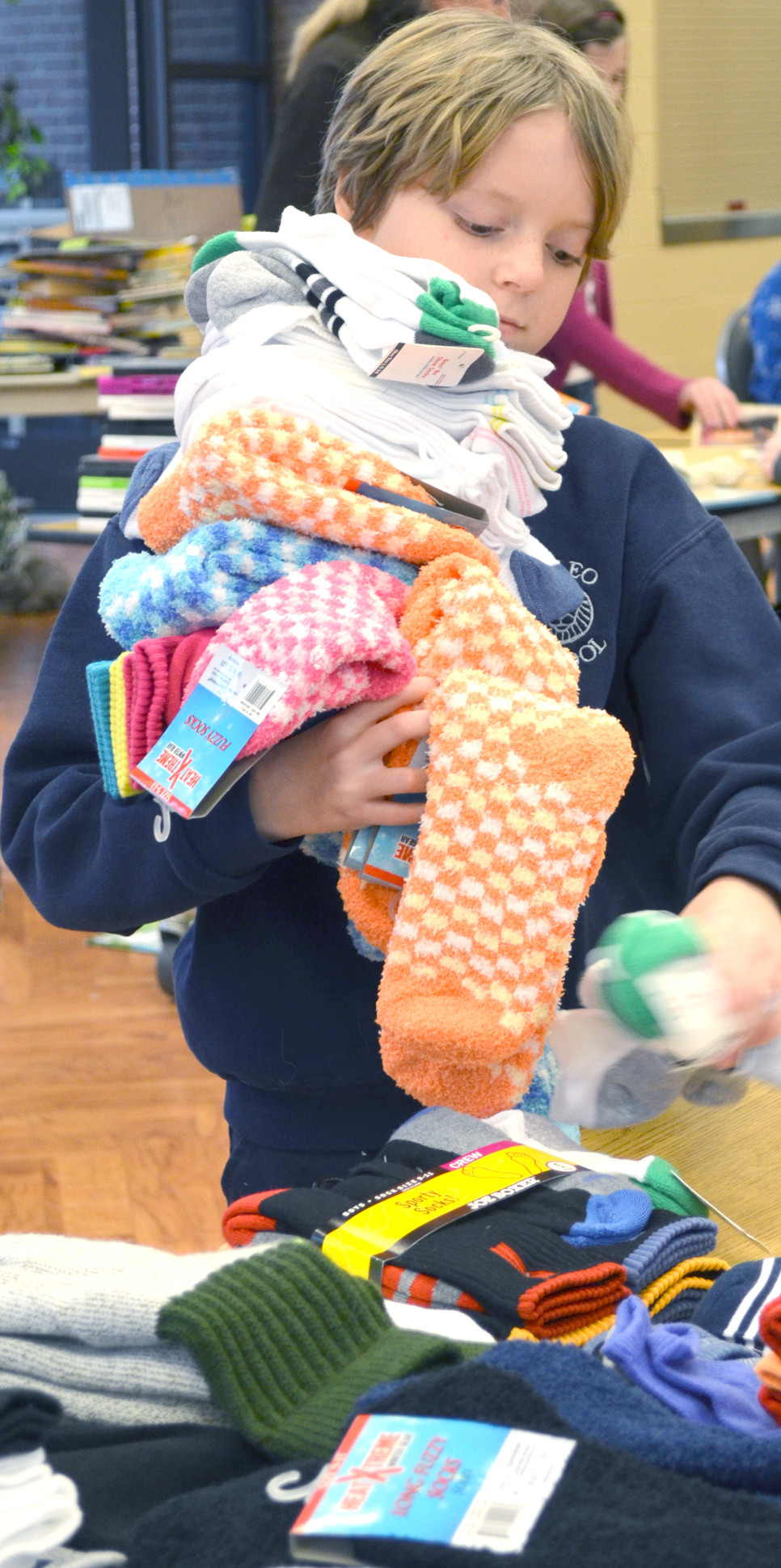 SARAH GREGORY, a fifth-grader at St. Leo School, carried an armload of socks while helping to sort donated items for this year's Christmas Store last week. (Photo by Bob Vlach)