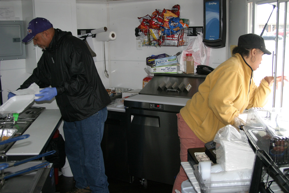 """FOOD TRUCK OWNERS and operators Terry Givens and Tamara Raglin did a brisk business on """"Fish Friday"""" at the Woodford Plaza. Givens, left, prepared a lunch box for delivery, while Givens took an order from a walk-up customer. (Photo by John McGary)"""