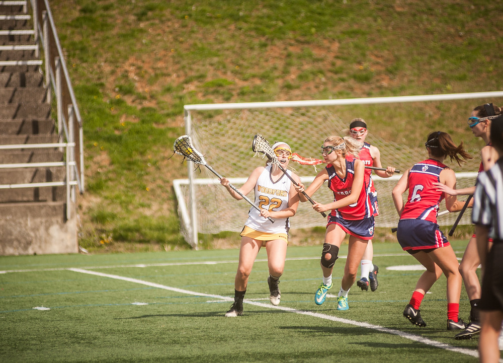WCHS JUNIOR ABBEY PETERSON battles a Lady Bearcat defender in Woodford's 11-6 win on Saturday, April 21 at Community Stadium. She scored five goals in the game for the Lady Jackets (Photo by Bill Caine)
