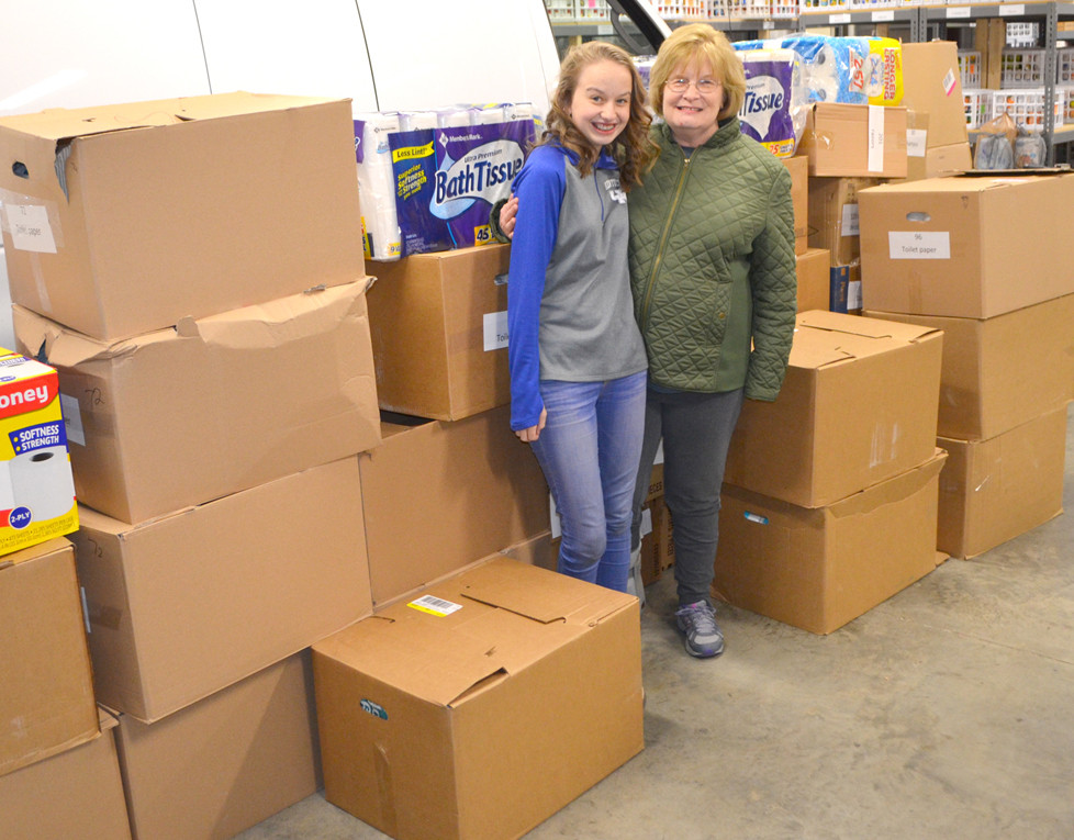 TARA BARBOUR, 16, and her family continued their annual tradition of delivering personal care items to the Food Pantry for Woodford County. Monetary donations to Tara's Toiletry Drive allow Tara to shop for the best bargains on soap and other personal care items so less-fortunate families won't do without. Tara is pictured with Sharon Hardin, director of the local food pantry. (Photo by Bob Vlach)