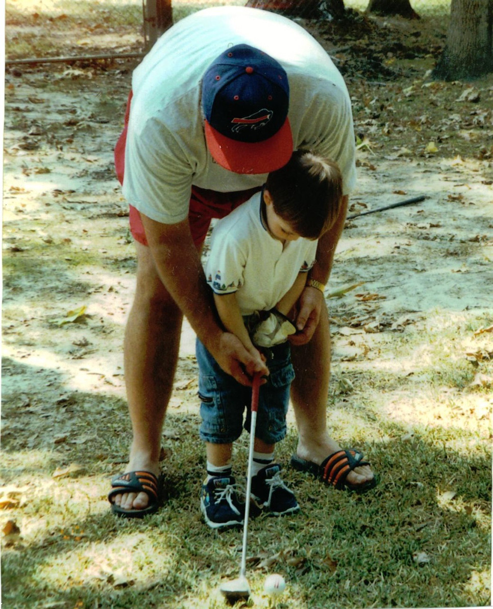 CRAIG RUSH helps an 18-month-old Corey with his golf swing. (Photo submitted)