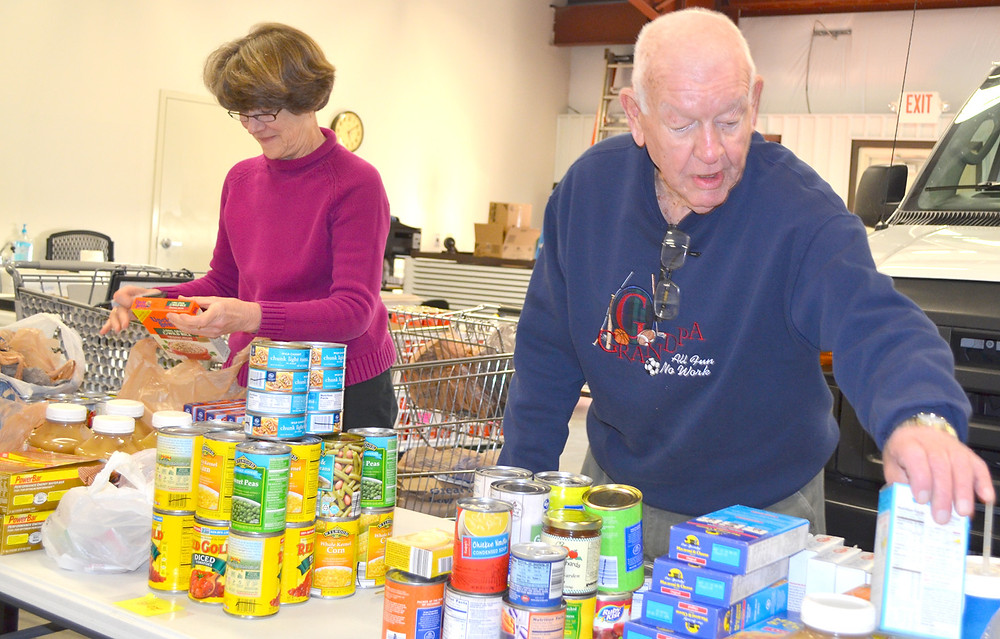 """VOLUNTEERS Dick Brock, right, and Helen Miller worked in the warehouse at the Food Pantry of Woodford County on Monday evening. """"I like the idea that when people get into a little bit of trouble (financially) that there's some place where they can go to get help,"""" said Miller. (Photo by Bob Vlach)"""