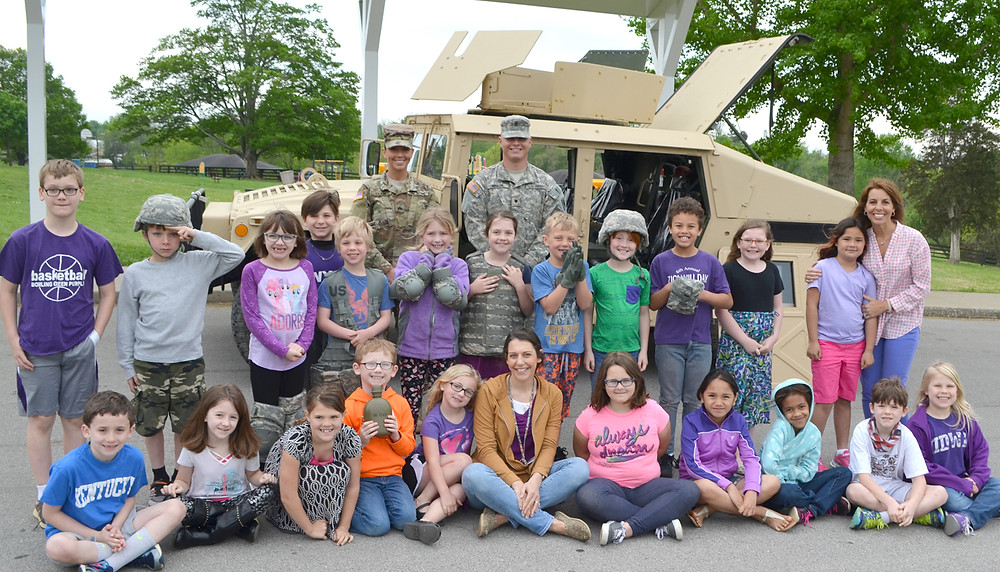 """SECOND-GRADERS at Northside Elementary School stood in front of a Humvee, with Army National Guard soldiers SPC. Robert Martin and Sgt. Whitney Click last Friday, April 21. The National Guard's visit came on """"Purple Up Day,"""" which happens during Month of the Military Child. (Photo by Bob Vlach)"""