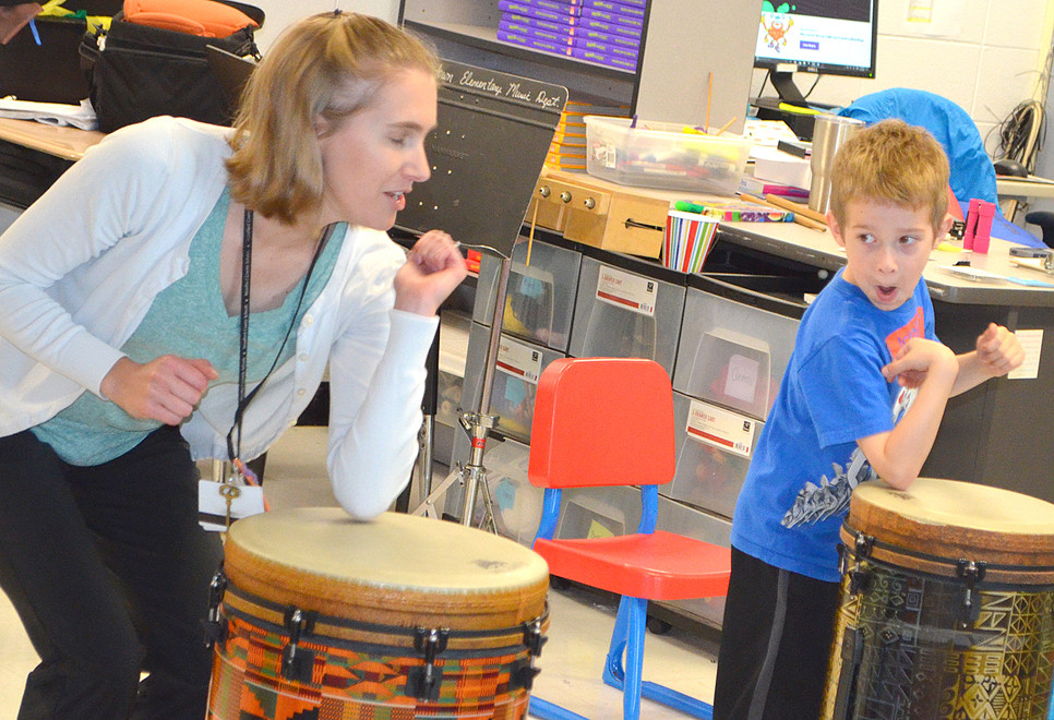 """JASE KUNTZ, a first-grader at Huntertown Elementary School, played a drum with his elbow in music class. """"...I want them to know that their ideas are important. That they are capable of making the music,"""" says music teacher Shannon Stieha. (Photo by Bob Vlach)"""