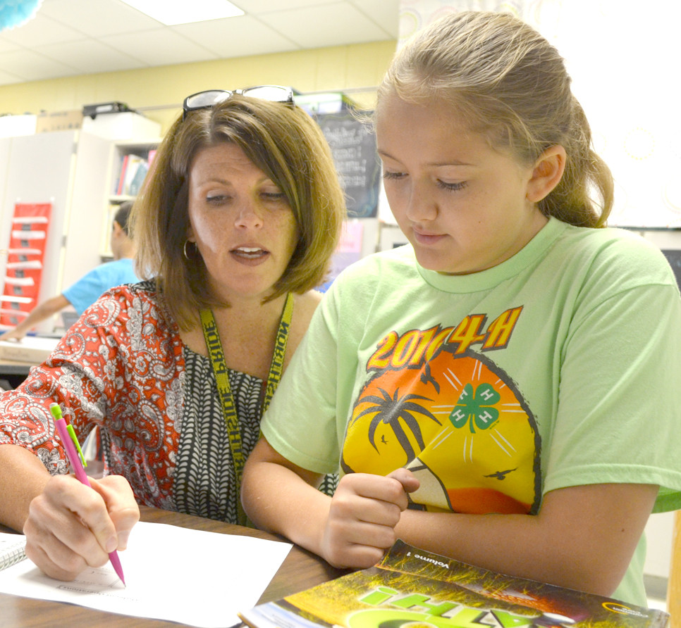 "HEATHER MOFFETT, pictured with fifth-grader Gracie Fetters, focuses on the individual needs of her students, and describes herself as ""their number one cheerleader."" (Photo by Bob Vlach)"