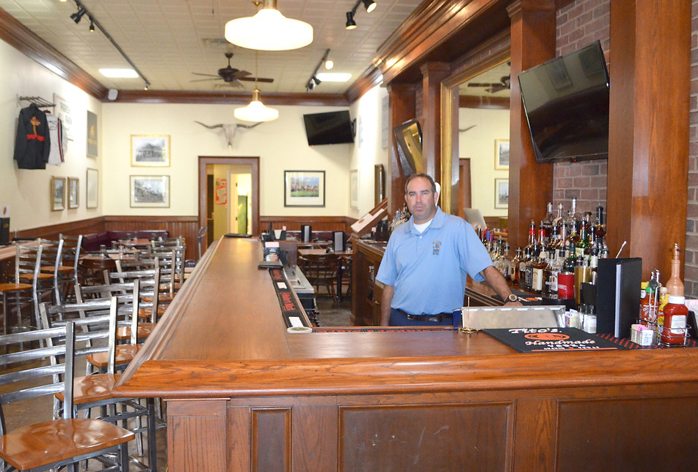 J.P. GIBSON stands behind the bar at Blind Harry's, which together with The Brown Barrel, recently opened on North Gratz Street in Midway. He wants The Brown Barrel/Blind Harry's to become an eatery where everyone – families and college students alike – can enjoy a meal at reasonable prices. (Photo by Bob Vlach)