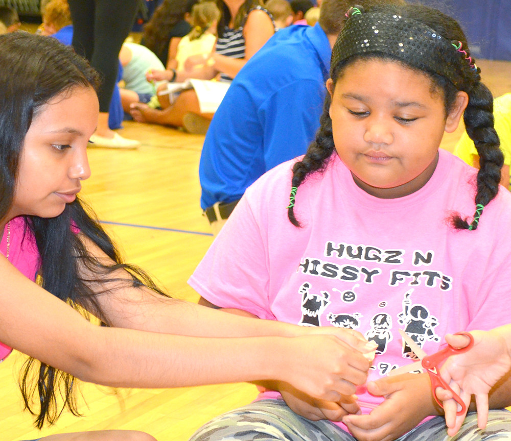 ARIANA DISCIPLINA, a student at Woodford County High School and a former PAWS participant, now volunteers in the summer program at Simmons Elementary. Ariana, left, helped Shianna White during a hands-on sailboat building project last Thursday morning. (Photo by Bob Vlach)