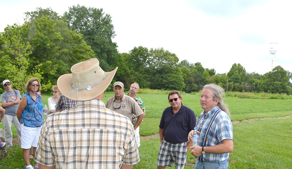 WALTER BRADLEY PARK was one of several stops on Monday's 52nd annual Woodford County Farm Tour. Volunteer John Holloway, right, talked about efforts to nurture an environment of native grasses, shrubs and trees in the 30-acre park near downtown Midway. (Photo by Bob Vlach)