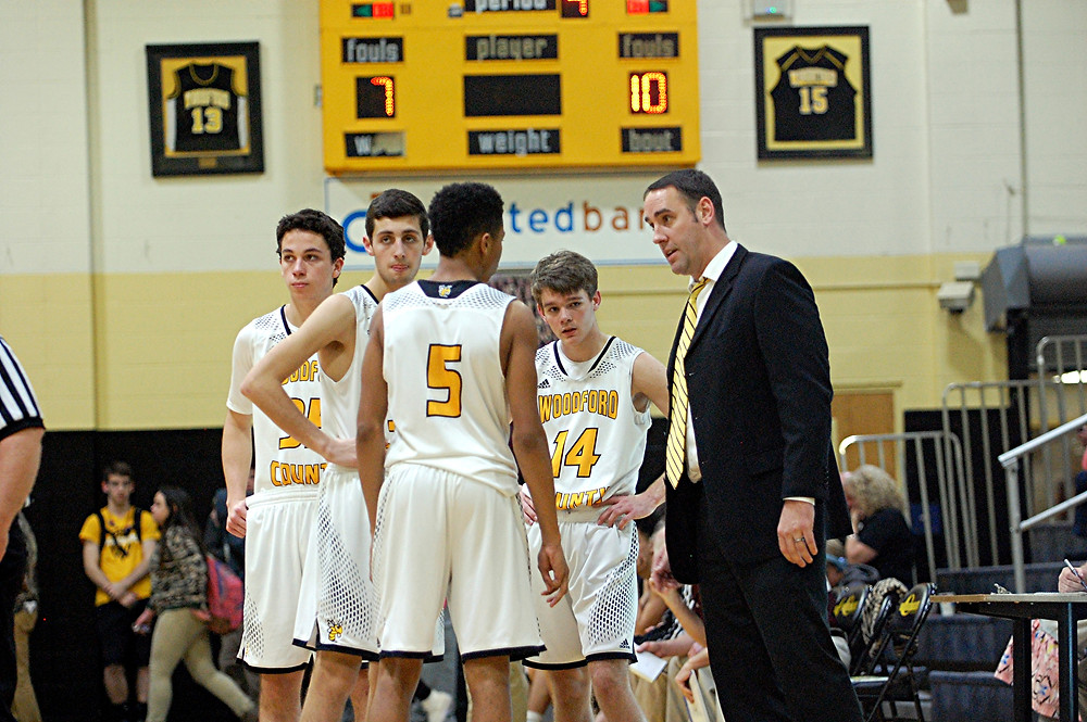 SCOTT HUNDLEY, right, head coach of the Woodford County High School boys' basketball team, huddles with his players during their game against Bourbon County at home in The Hive on Friday, Feb. 5. While the Yellow Jackets held the lead deep into the third quarter, the Colonels came back to win, 75-59. (Photo by Rick Capone)
