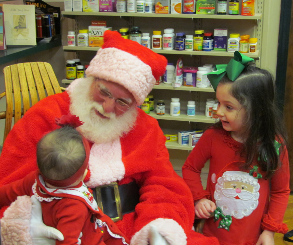 CHLOE  DEWEESE, right, watched baby sister Kensington have her first visit with Santa Claus at the Cornerstone Pharmacy on Dec. 11. A few seconds later, despite Santa's best efforts, Kensington decided she'd had enough. The visit was part of an annual tradition there. (Photo by John McGary)