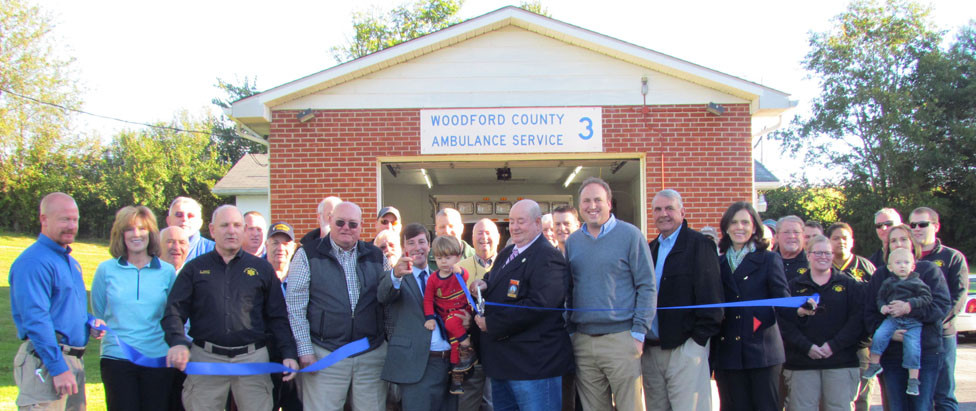 "FUTURE WOODFORD JUDGE-EXECUTIVE James Kay, holding a pair of scissors and his son, cut the ribbon for the new Midway EMS station that opened last Friday, Oct. 19. To his left is present Judge-Executive John Coyle, who called the opening and the plan to build a new county fire station in the western portion of the county park a ""win-win"" for everybody. (Photo by John McGary)"
