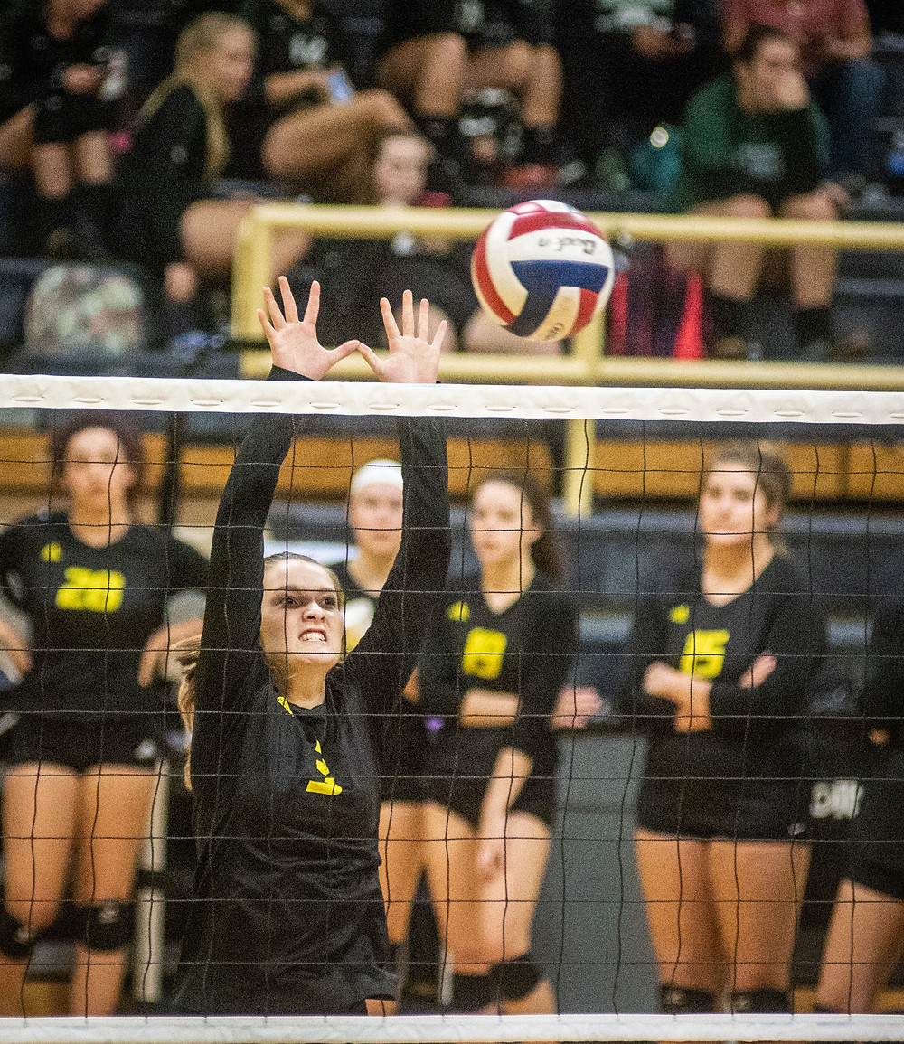 WCHS SENIOR ZOE HARPER attempts a block at the net during the Woodford County Invitational tournament Sept. 8. (Photo by Bill Caine)