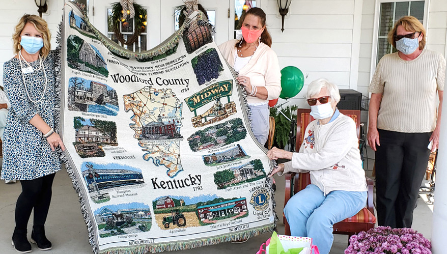 A TAPESTRY OF WOODFORD COUNTY SITES was given to Mimi Hackney during a drive-by parade at Daisy Hill Senior Living to celebrate her 90th birthday on Oct. 21. Pictured from left are Daisy Hill Executive Director Laurie Dorough and resident service Director Jane Washington, with Mimi and daughter-in-law Tara Hackney. (Photo submitted)