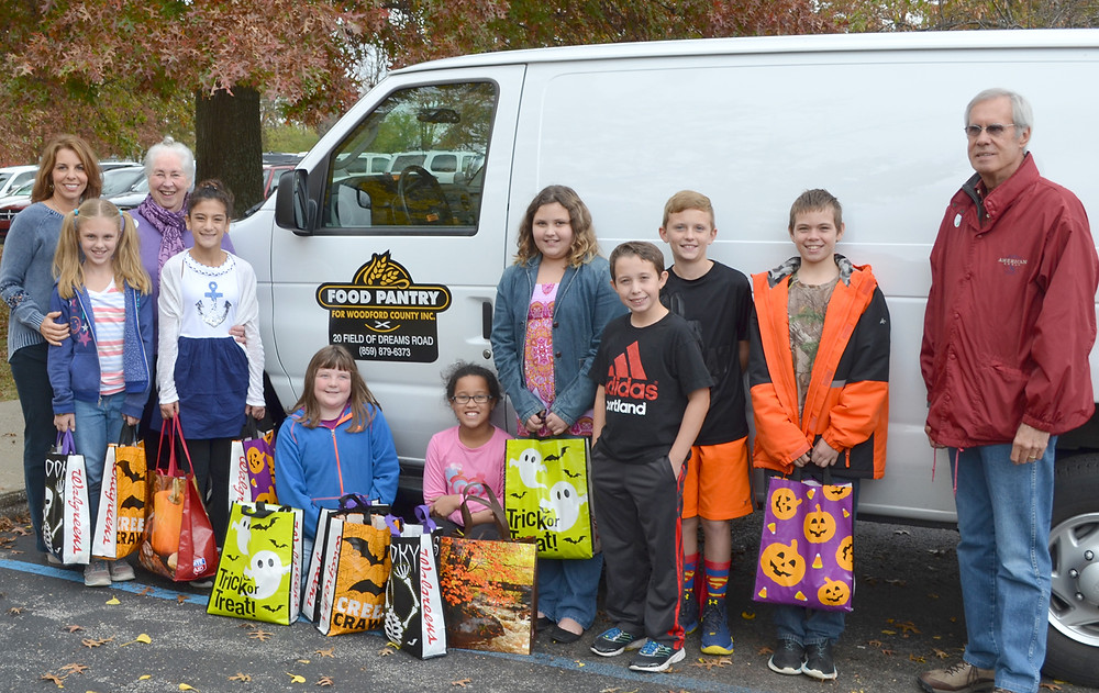 NORTHSIDE ELEMENTARY School's student-leaders coordinated a Halloween candy drive that resulted in 81 pounds of sweet treats being donated to the Food Pantry for Woodford County. From left, front, are Lighthouse Team members Kaylin Shuck, Annika Loyet, Emma Mulvihill, Cora Morton, Haley Brown, Jack Buckley, Ethan Johnson and Kody Hager; standing behind the Northside fifth-graders are guidance counselor Mindy Woodall, left, Peggy Carter Seal and Bill Phelps, at far right, who are volunteers at the Food Pantry for Woodford County. (Photo by Bob Vlach)
