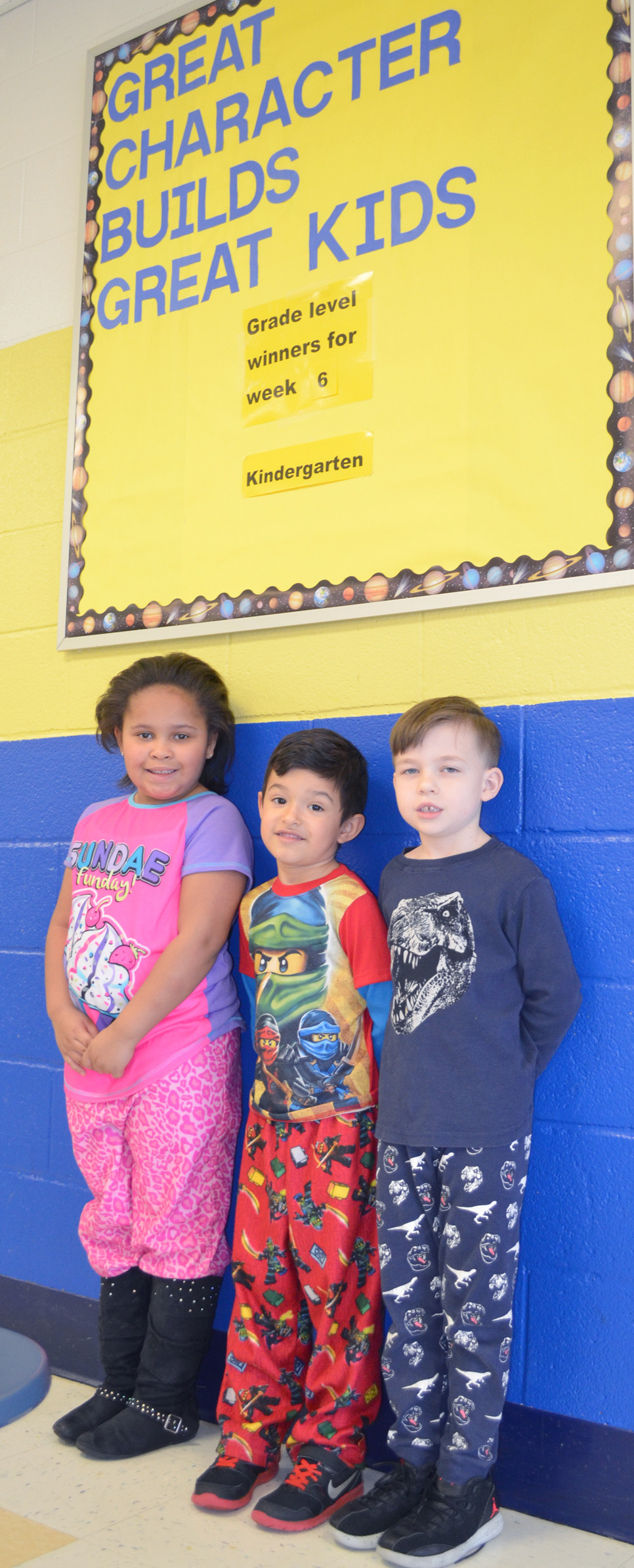 SIMMONS ELEMENTARY School first-graders Aaliyah Fisher and Kalel Hawkinson and kindergartner Leland Markwell recently explained what empathy, responsibility and kindness mean to them. Students are awarded mastery cards whenever they demonstrate an understanding of a positive character trait or value they've learned in school. (Photo by Bob Vlach)
