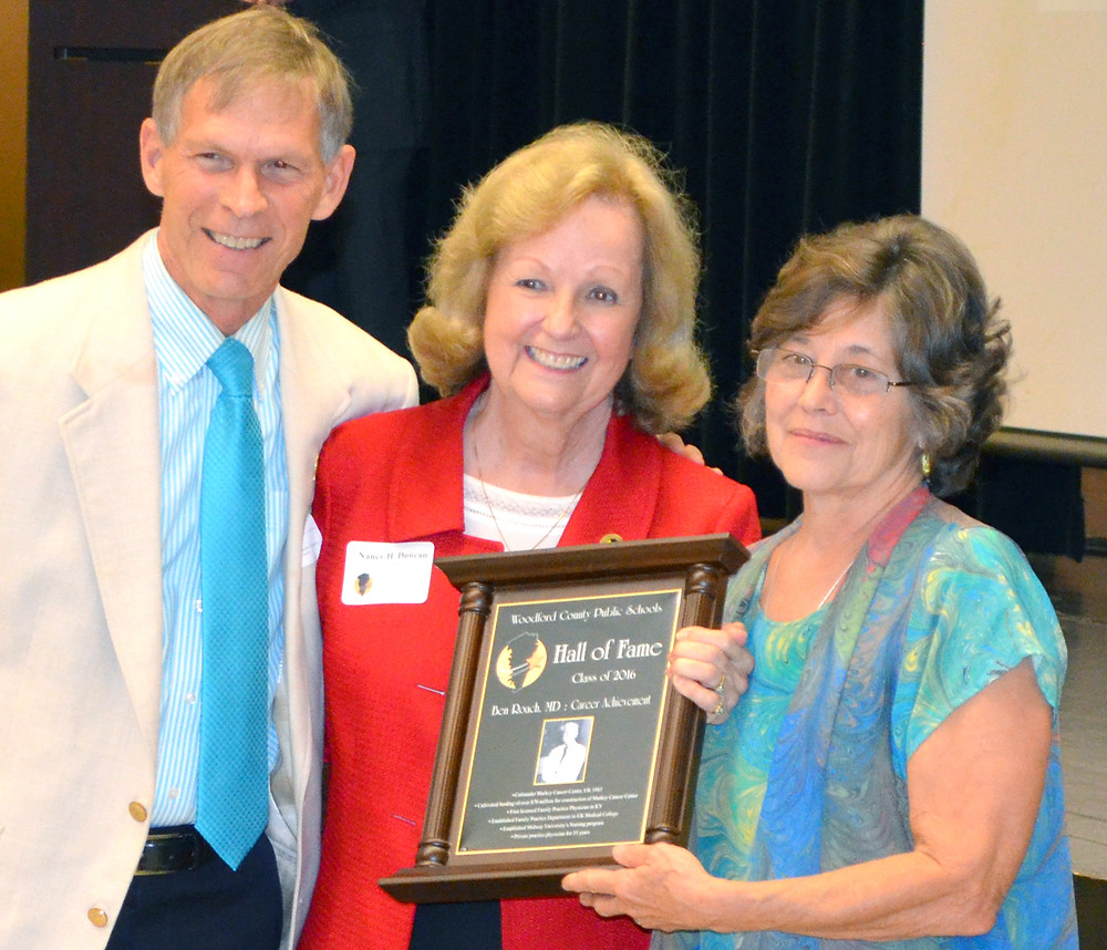 ACCEPTING A HALL OF FAME PLAQUE on behalf of the late Dr. Ben Roach, are his children, Jim Roach and Helen Roach Rentch, right. Nancy Duncan, co-chair of the WCPS Hall of Fame committee, center, presented the award. (Photo by Bob Vlach)