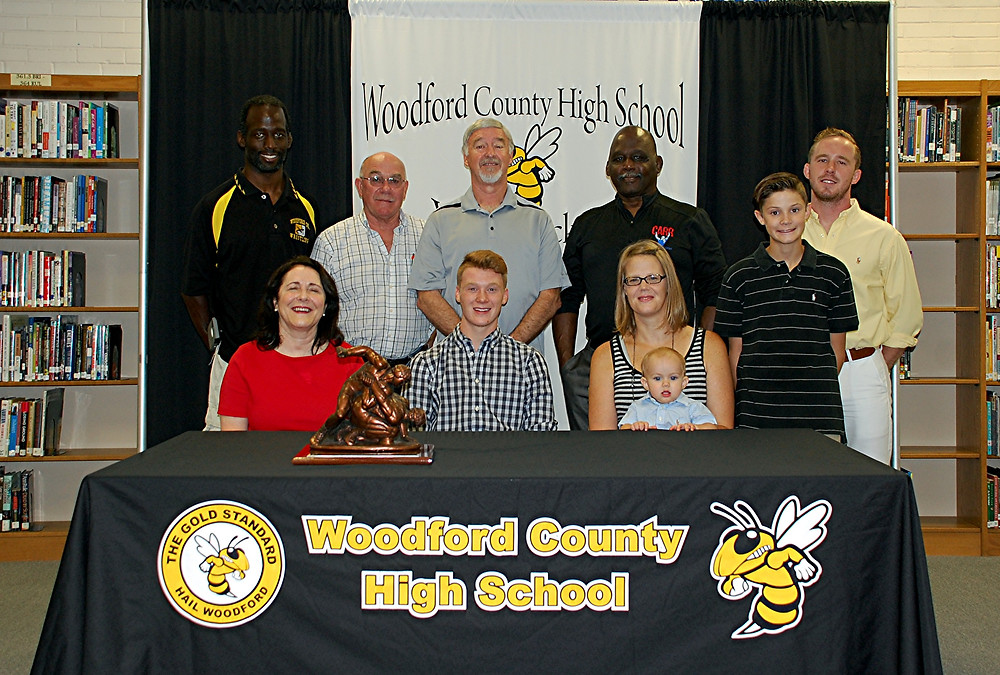 TUCKER HURST, seated middle, a senior wrestler on the Woodford County High School wrestling team, was named the 13th recipient of the Michael Jackson Memorial Scholarship award on Tuesday, June 19. Shown in the photo with Tucker are front row, from left, Debbie Jackson; Addie Martin, Tucker's mom; and his brothers, Tripp Martin and Trey Martin; back row, Joe Carr Jr., Randy Cotton; Rusty Parks Sr.; Joe Carr Sr.; and Rusty Parks Jr. (Photo by Rick Capone)