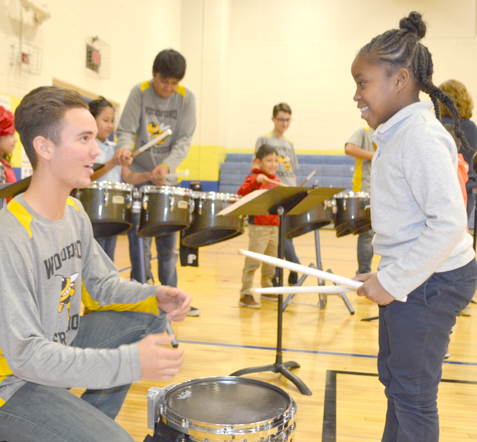 WCHS SENIOR Trace Miller gave Simmons Elementary School second-grader DaeJa'Nae Carter an opportunity to play a snare drum during Arts Day on Nov. 21. Guest artists, including professionals and students from Woodford County middle and high schools, introduced students to a variety of performing and visual arts. (Photo by Bob Vlach)