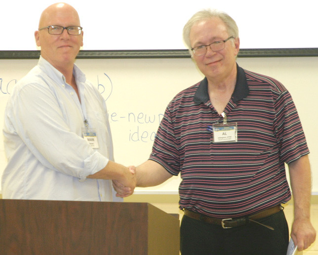 AL EDINGTON, right, who suffered a severe stroke in December of 2014, shook hands with Midway Toastmaster Dr. Mark Roozen after his comeback speech Monday night. Edington told fellow members that when you get knocked down, you can't stay down. (Photo by John McGary)