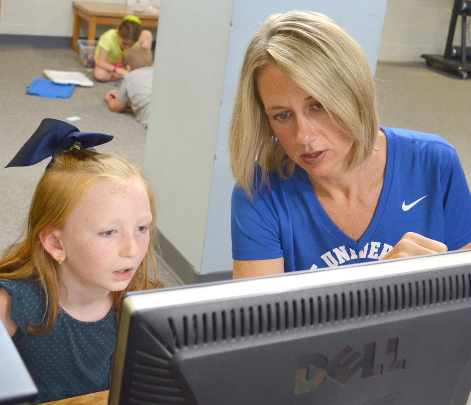 """SECOND-GRADER Harper Lacefield got some help with her computer coding from library media specialist Candy Luttrell last Friday at Southside Elementary School. """"I like the hugs. I like the excitement,"""" says Luttrell of being an elementary school educator. Southside's Teacher of the Year lives in Versailles with her husband, Walter, and daughter, Samara. (Photo by Bob Vlach)"""