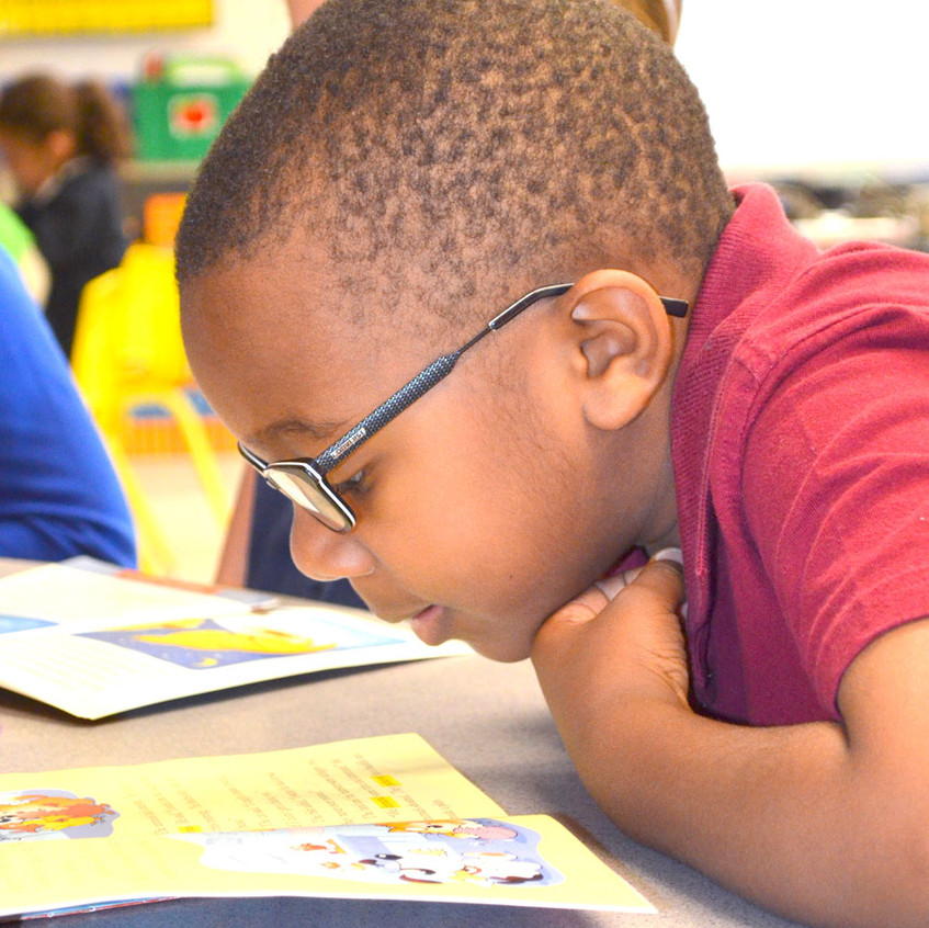 A READING FOCUS at Simmons Elementary includes many different guided reading strategies. First-grader Traiden Caywood reads during a recent two-hour block, which has been set aside to focus on literacy at all grade levels every morning at Simmons. (Photo by Bob Vlach)