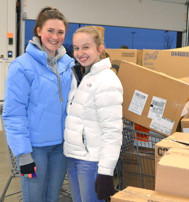 TARA BARBOUR, right, and Chiara Heidenreich, a foreign exchange student from Austria staying with Tara's family, stood next to boxes filled with 18,593 personal care items donated to the Food Pantry for Woodford County Nov. 26. Tara's family delivered her donation, which has become a holiday tradition for them. (Photo by Bob Vlach)