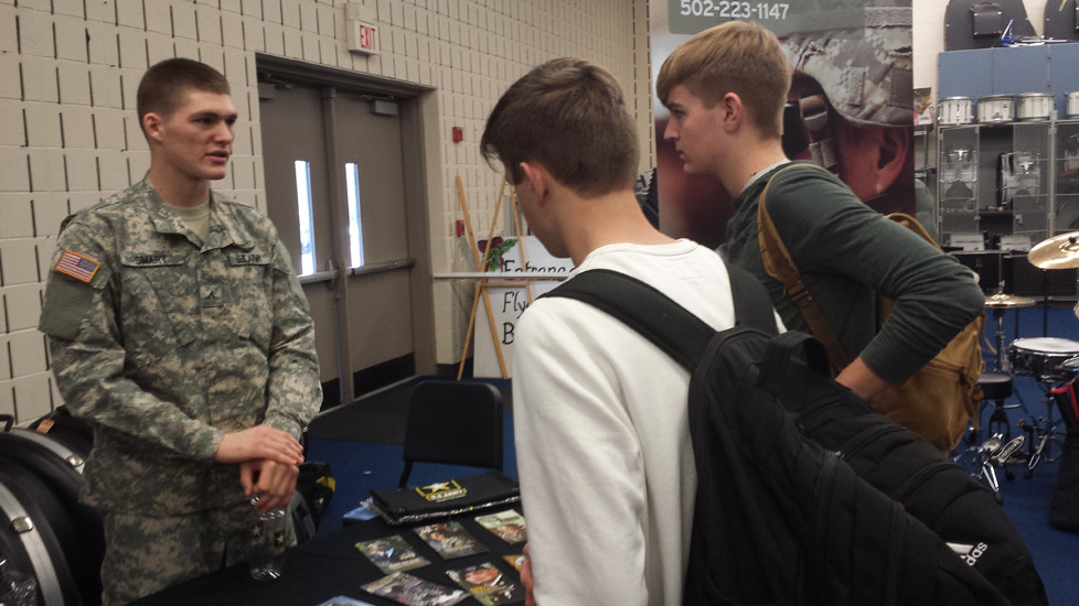 PVT. BENJAMIN SMART, left, talks to Franklin County High School students during a recent recruiting event. A Versailles native and 2015 graduate of Woodford County High School, Smart is back in Central Kentucky assisting local Army recruiters. (Photo by Lee Elder, USARB Nashville public affairs)
