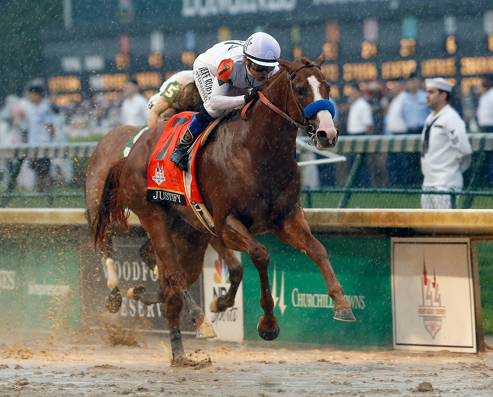 WINSTAR FARM'S JUSTIFY won the 144th Kentucky Derby Saturday, fending off late challenges by Audible, seen here just behind Justify, and Good Magic, which finished second. The wettest Kentucky Derby on record was also the sixth in a row won by the favorite. There's much more on the Derby in Sports on page 15. (Photo by Charles Bertram, Lexington Herald-Leader)
