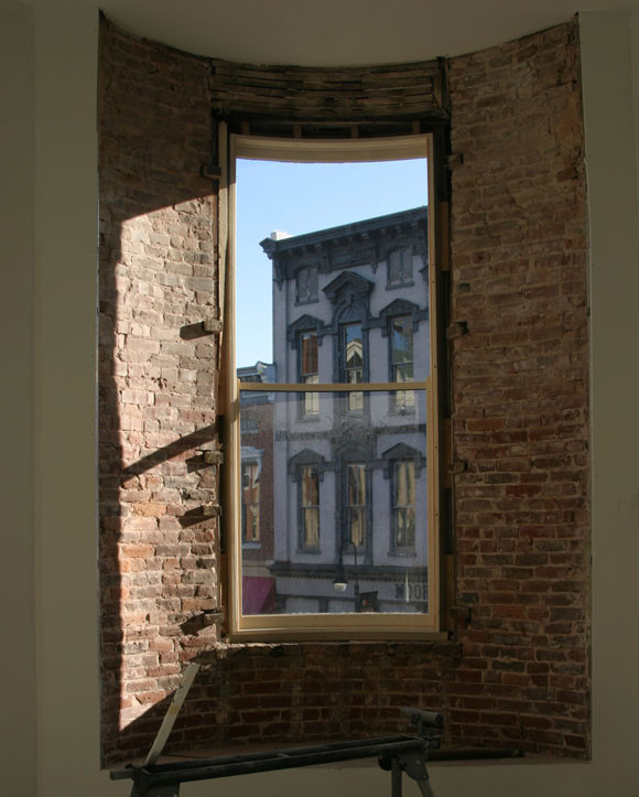 THE UPSTAIRS ROOM on the South Main Street side of the Amsden Building features the building's original brick walls and a view of some of the other historic buildings in downtown Versailles. Three tenants will occupy the upstairs area, with three new businesses below. (Photo by John McGary)