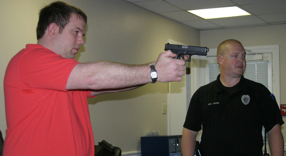 """EVERY YEAR, officers from the Versailles Police Department spend a few hours with FATS - a firearms training simulator provided by the Kentucky League of Cities to departments across the state. """"It's a great training tool for officers for decision-making,"""" said lead firearms instructor Officer Nathan Craig. Before beginning the first simulation, Craig gave Versailles Mayor Brian Traugott a little target practice with a laser-armed pistol. (Photo by John McGary)"""