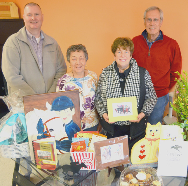 """THE VERSAILLES LIONS CLUB and Food Pantry for Woodford County are hosting a Derby Breakfast and silent auction at the First Christian Church Life Center on Saturday, May 5. Pictured, with a few of the many items up for auction are, from left, Wayne """"Tiny"""" Wright of the Lions Club; Mary Ann Myhre and Missy Trumbore, coordinators of the silent auction; and Bill Phelps, president of the food pantry board. (Photo by Bob Vlach)"""