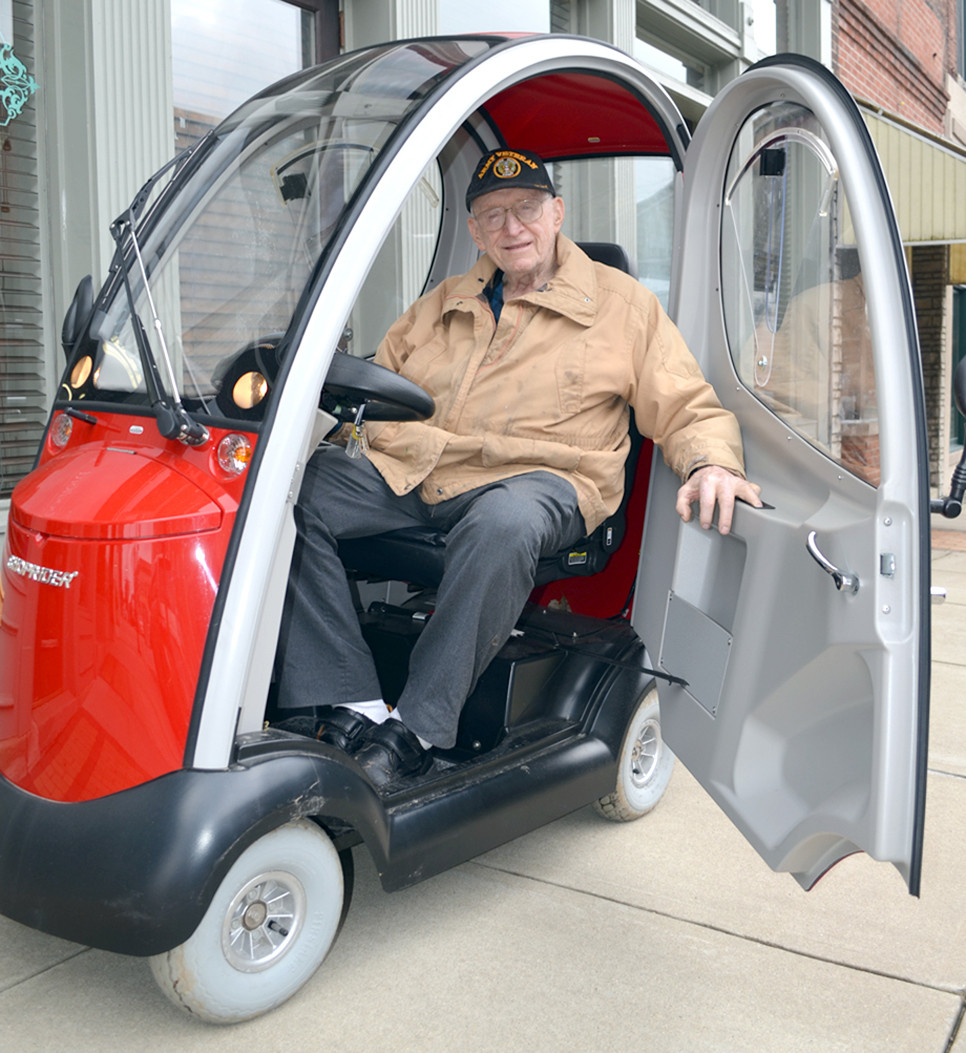 """JIM SILLS motors around downtown Versailles in his scooter. The """"Flagship"""" scooter can go up to 10 miles per hours, but """"I go about 5,"""" says Sills. He's been told a single charge will allow him to travel 100 miles, but he has his doubts. (Photo by Bob Vlach)"""