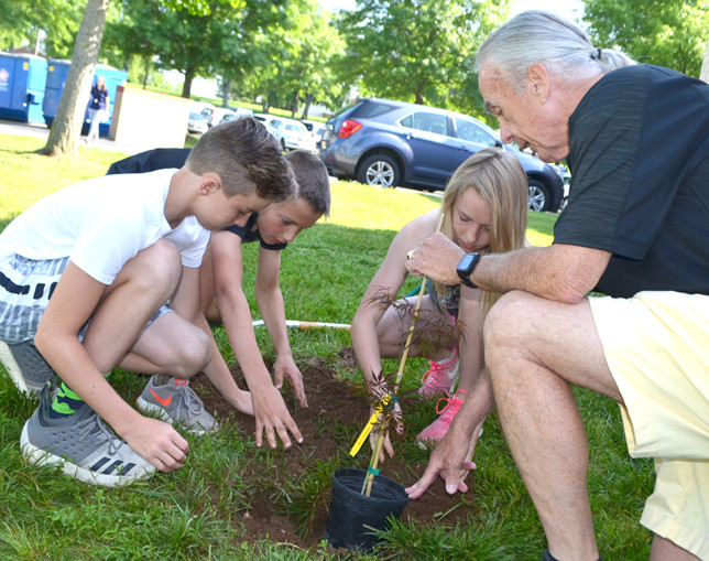 AMBROSE WILSON IV helped Northside Elementary School fifth-graders, from left, Nolan Asher, Charlie Twehues and Payton Asher plant a Japanese maple on May 23 to honor the longtime chair's 25 years on the Woodford County Board of Education. (Photo by Bob Vlach)