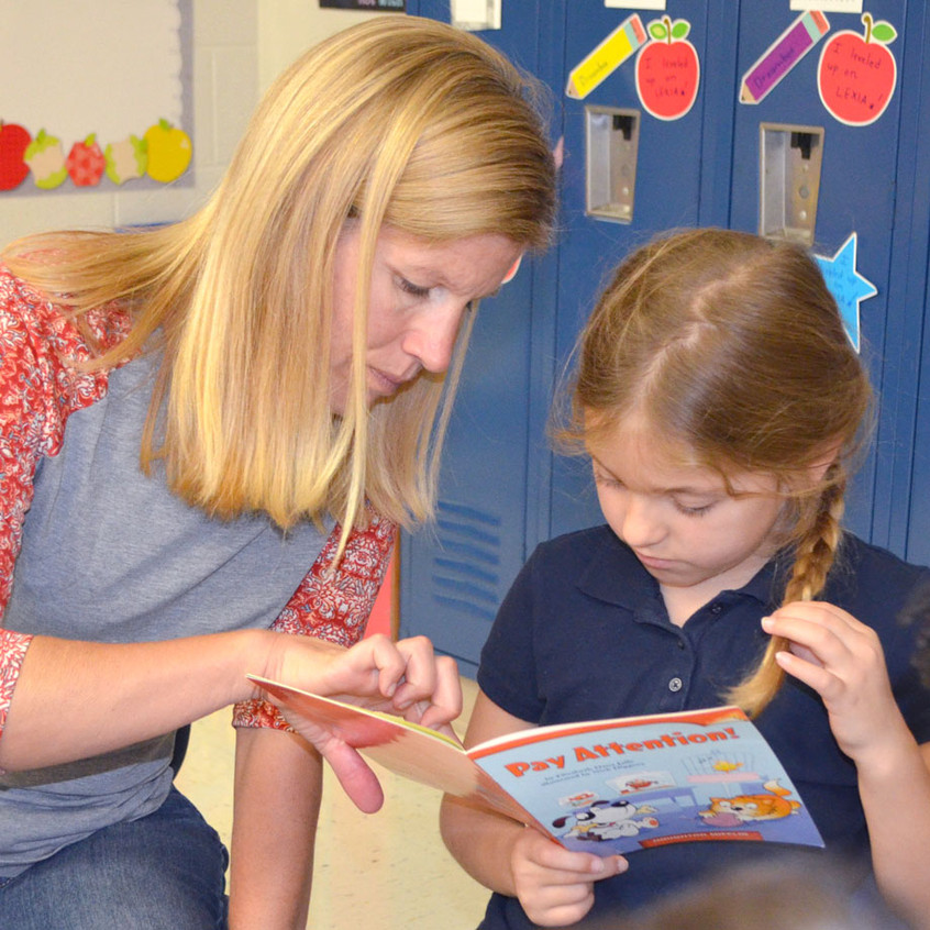 FIRST-GRADE TEACHER Kim Haury provided one-on-one reading guidance to Aubree Sears during a recent two-hour literacy block in her classroom at Simmons Elementary School. (Photo by Bob Vlach)