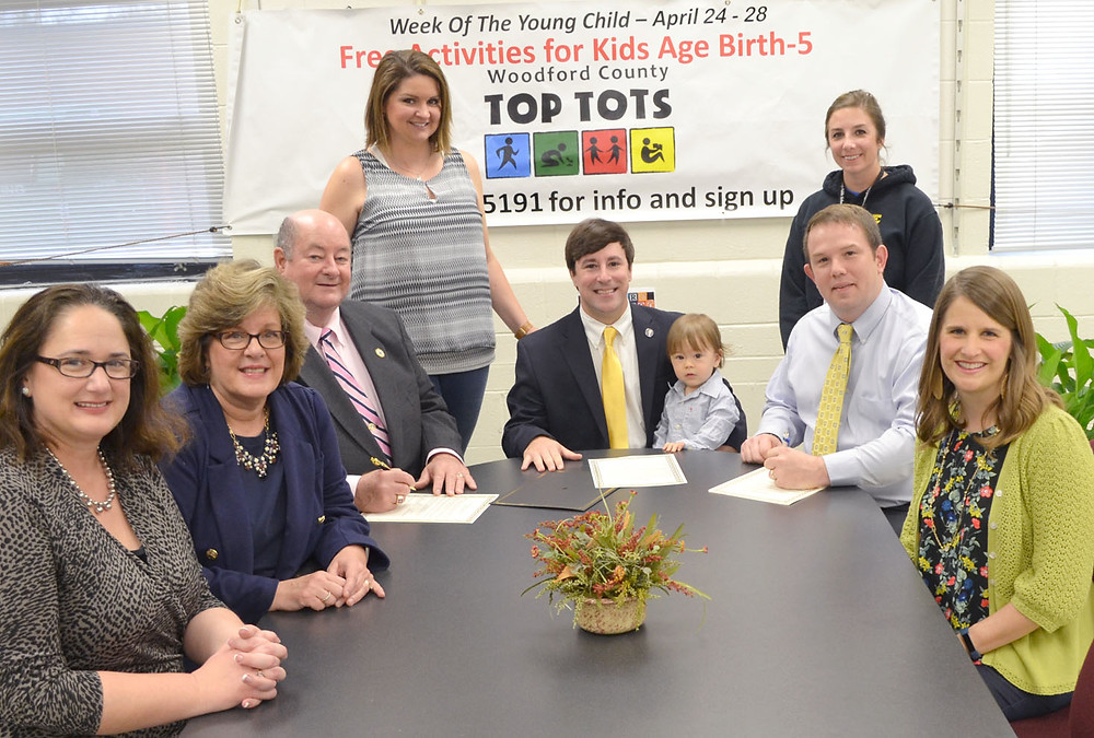 """'WEEK OF THE YOUNG CHILD' is being observed in Versailles, Midway and Woodford County, from April 24 to 28. A proclamation signed by Woodford County Judge-Executive John Coyle and Versailles Mayor Brian Traugott encourages """"all citizens to work to make a good investment in early childhood development in our community."""" From left are Simmons Elementary School Principal Tiffany Cook; Kathy Hogg, coordinator of district programs in Woodford County schools; Coyle, Simmons preschool teacher Kim Johnson, state Rep. James Kay, with his 16-month-old son, Kieran; Family Resource Coordinator Chelsea Burke, Traugott; and Courtney Nuckols, Top Tots grants manager. (Photo by Bob Vlach)"""