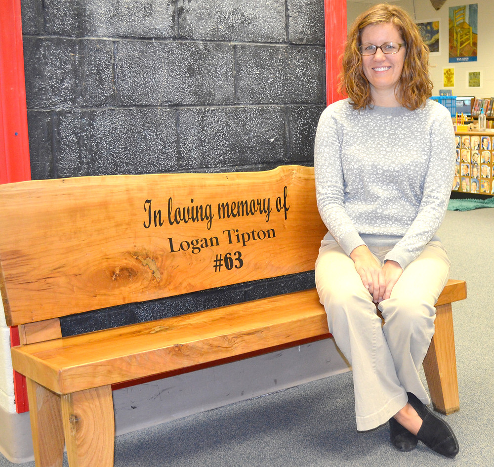 A BENCH IN MEMORY of Logan Tipton has become a special place where students read in the library at Simmons Elementary School. Librarian Mindy Logan, pictured, has helped sort thousands of plastic caps donated to a fundraiser for a planned outdoor memorial to remember 6-year-old Logan Tipton, who was killed in his family's home last December. (Photo by Bob Vlach)