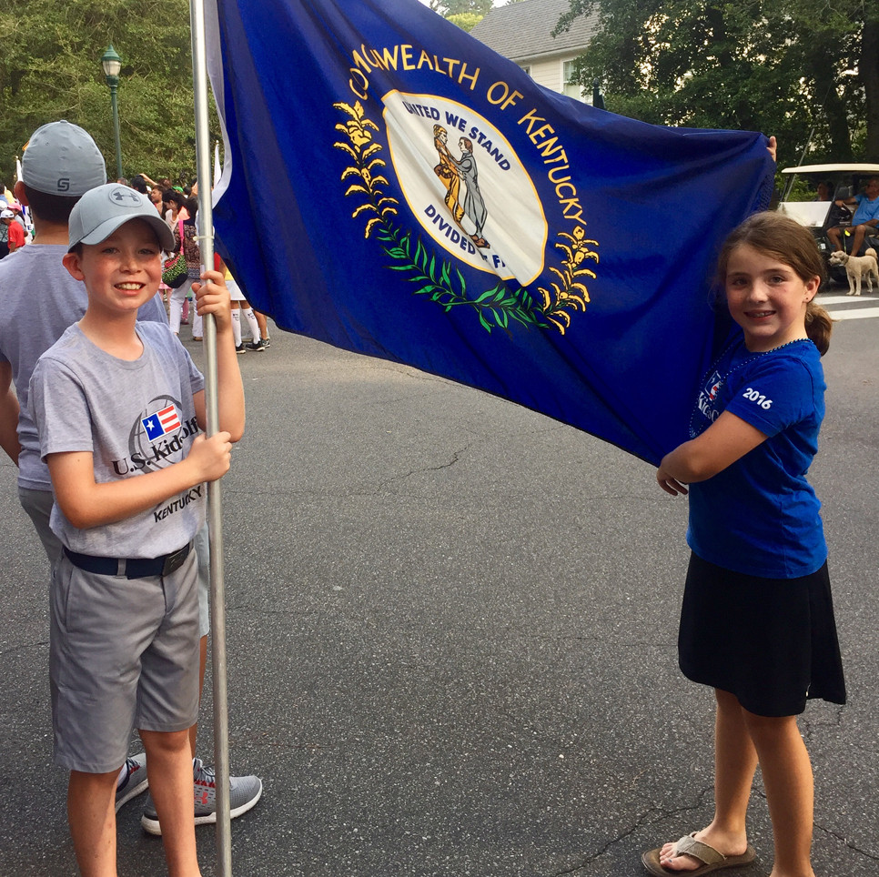 BRADFORD LACEFIELD and Abigail Caine pose with the Kentucky state flag at the Parade of Nations that officially starts the USKids Golf World Championship week.  (Photo submitted)