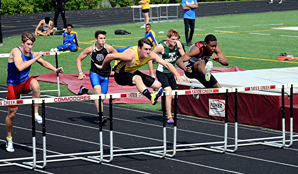 LANDON SAUM, center, shown running the hurdles at the Commodore Classic at Tate's Creek in Lexington on Saturday, April 15, won the 110-meter hurdles for the Woodford County High School track team at the Tomahawk Challenge, which was held at Montgomery County High School in Mt. Sterling on Thursday, April 20. His winning time of 15:30 broke the existing WCHS record and the Tomahawk Challenge record. (Photo by Michael Gormley)