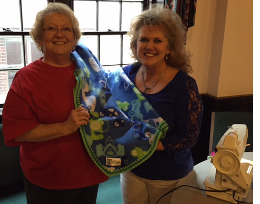 """PROJECT LINUS organizers, from left, Mary Ann Overturf and Theresa Range show off one of their handmade blankets. Others will be collected at """"Make a Blanket Day"""" Saturday from 10 a.m. to 3 p.m. at St. John's Episcopal Church. (Photo submitted)"""