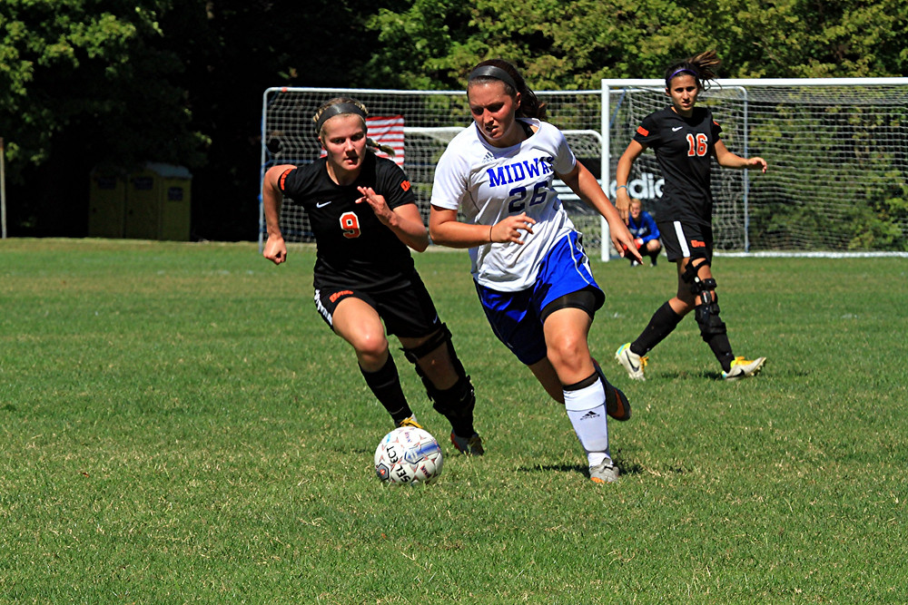 KINDSAY MILLER-RINEY, white jeersey, dribbles the ball during Midway University's women's soccer game against Pikeville on Thursday, Sept. 22. The junior scored the game winning goal to give the Eagles a 1-0 win over the Bears. (Photo by Steve Blake/multiexpoures.com)
