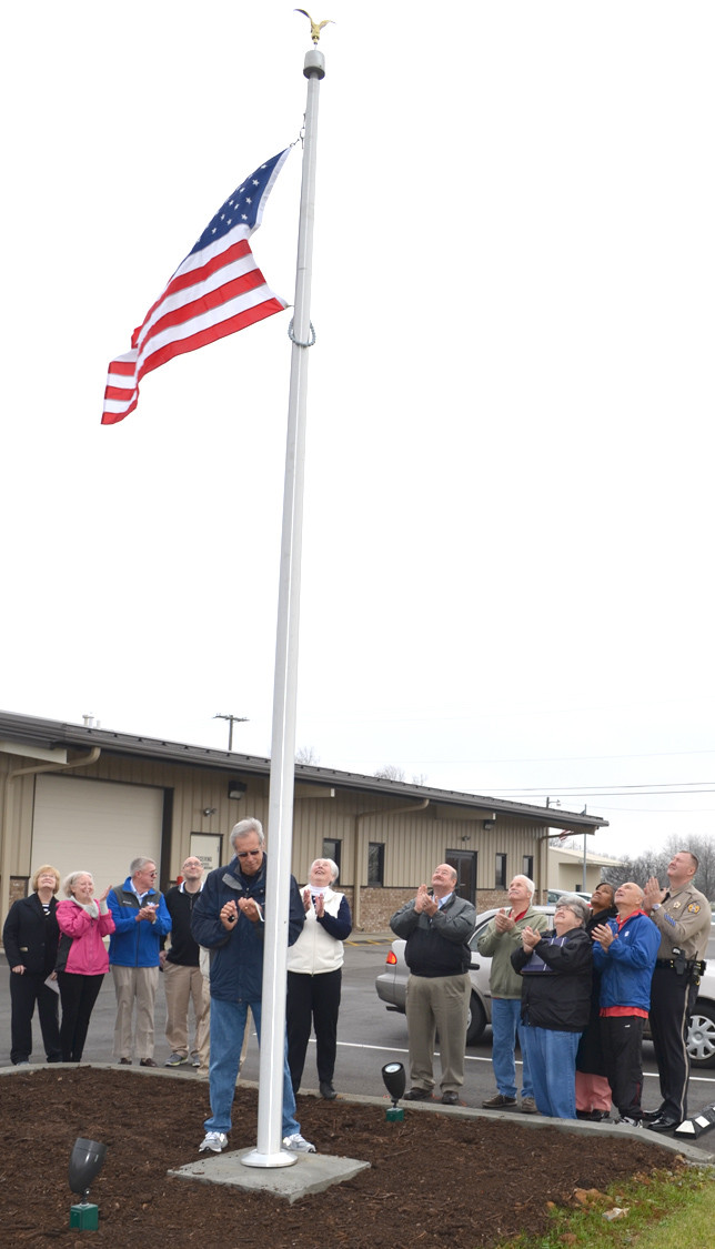 FOOD PANTRY VOLUNTEERS and other community members gathered at the Food Pantry of Woodford County on Thursday morning, Dec. 10, to dedicate a flagpole in memory of longtime volunteer Anthony J. Modica. The American Flag honors all food pantry volunteers – past, present and future. Volunteer Bill Furlong was lauded for his intense research into finding a suitable flagpole during last week's dedication ceremony. (Photo by Bob Vlach)