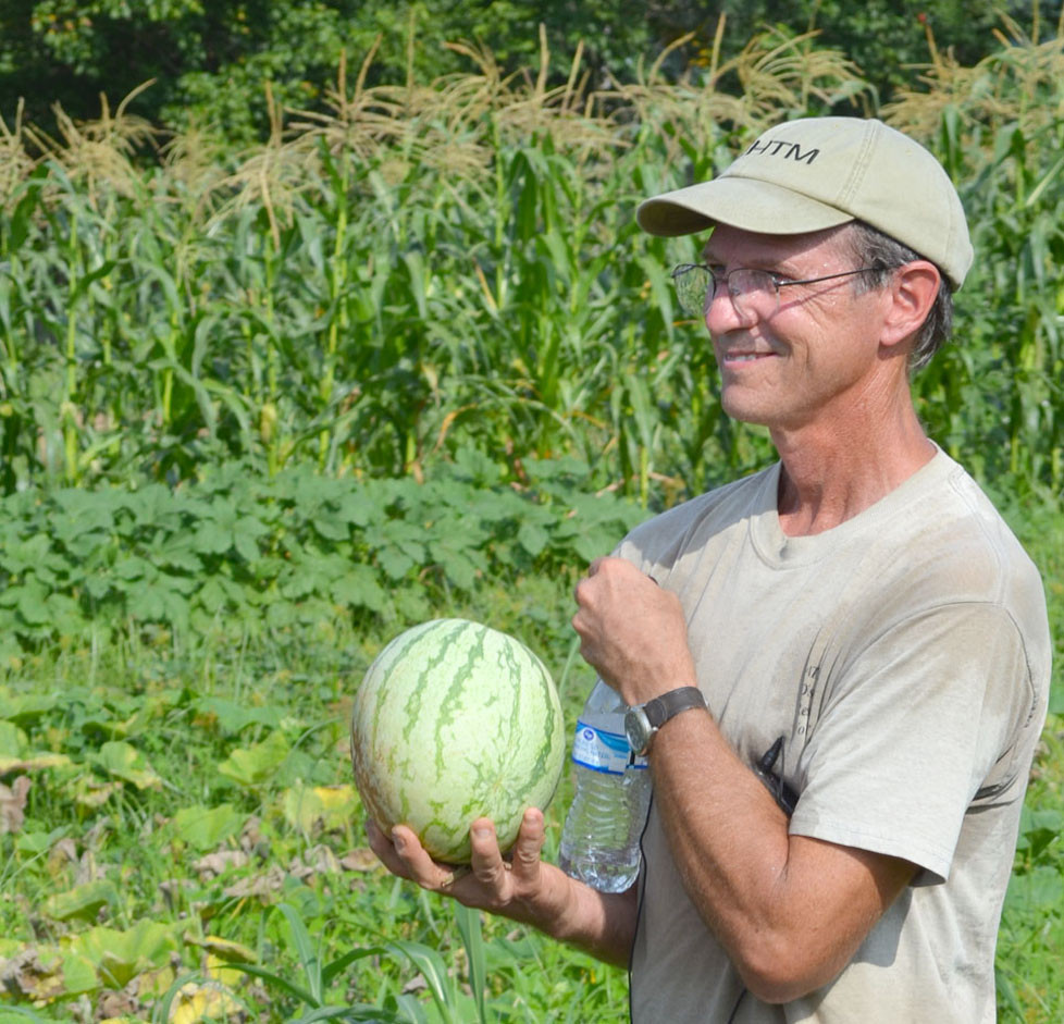 JOHN WILHOIT sells homegrown vegetables from Thistle's End Farm at the Woodford County Farmers Market. On Monday morning, Wilhoit held a watermelon picked from his vegetable garden. His and Sue Churchill's family farm was one of two stops on this year's Woodford County Farm Tour. (Photo by Bob Vlach)