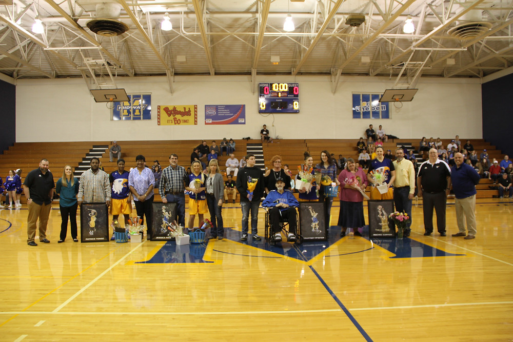 THE MIDWAY UNIVERSITY WOMEN'S BASKETBALL TEAM clinched a playoff spot with a 73-58 win on senior night against Brescia University. Coach, John Kenger, is joined by his four seniors prior to the game. (Midway Athletics photo)