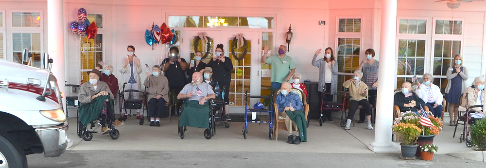 MILITARY VETERANS, joined by other residents of Daisy Hill Senior Living, waved to a parade of vehicles as they drove past on Veterans Day, Nov. 11. (Photo by Bob Vlach)
