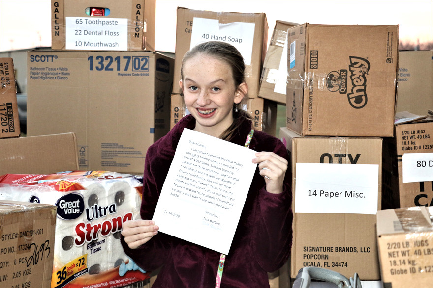 "TARA BARBOUR holds a letter written to the Food Pantry for Woodford County while helping to deliver 4,037 personal care items collected during Tara's Toiletry Drive. ""I am so glad that I get to pay it forward to the people of Woodford County,"" the Woodford County High School sophomore wrote in her letter. (Photo by Nora Hartley)"