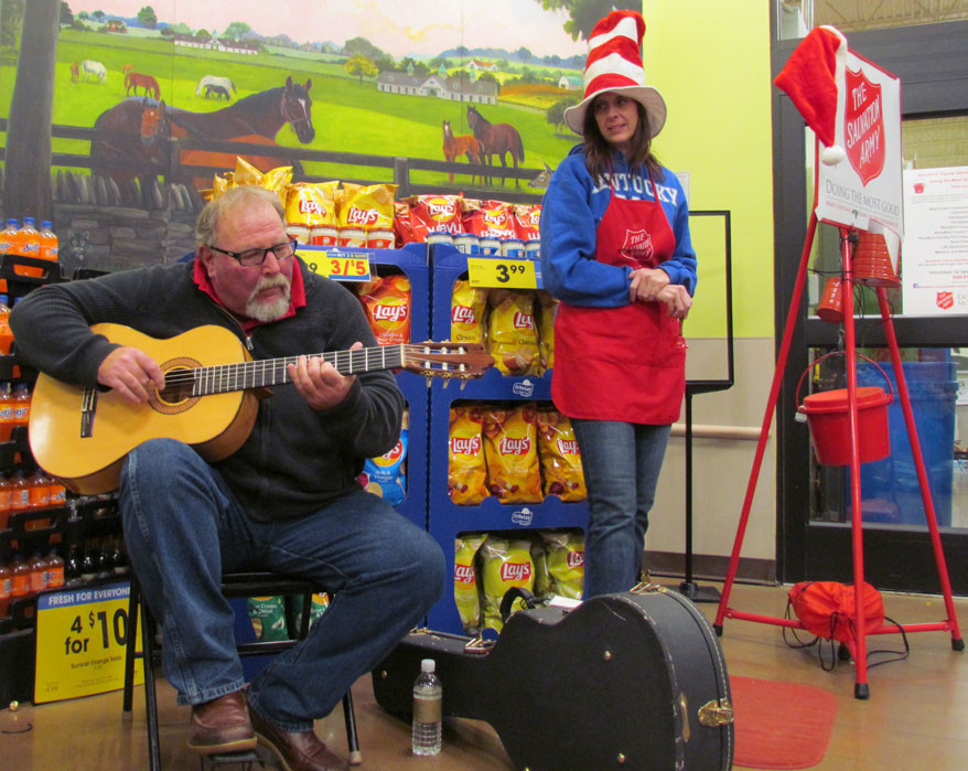"GUITARIST SAM HAWKINS entertained shoppers at Kroger a week before Christmas Day. Friend and fellow St. John's Episcopal Church member Tracy Clay, right, called him ""extremely talented."" The last two years, St. John's members have provided music for the Salvation Army's annual drive in Woodford County. (Photo by John McGary)"