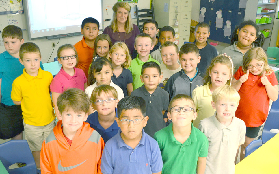 """KELSEY BREWER, pictured at back with her second-grade class, was named Teacher of the Year at Simmons Elementary School. She describes a teacher's job as """"meeting them at the level where they're at so that they can grow."""" (Photo by Bob Vlach)"""