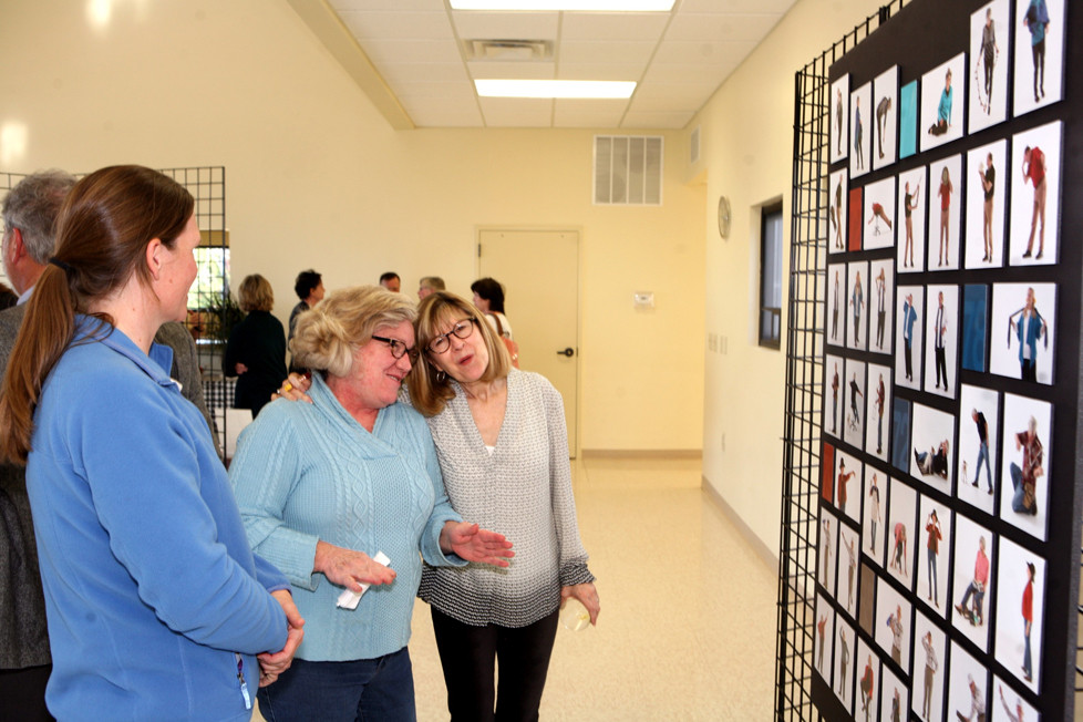 """DONNA BOOTH FARMER held an exhibition of her photography featuring seven Midway residents. The exhibition titled """"Youth of an Older Generation"""" took place at the Midway Presbyterian Fellowship Hall last Sunday. Farmer, right, discusses her work with two of the exhibition's attendees. (Photo by John McDaniel)"""